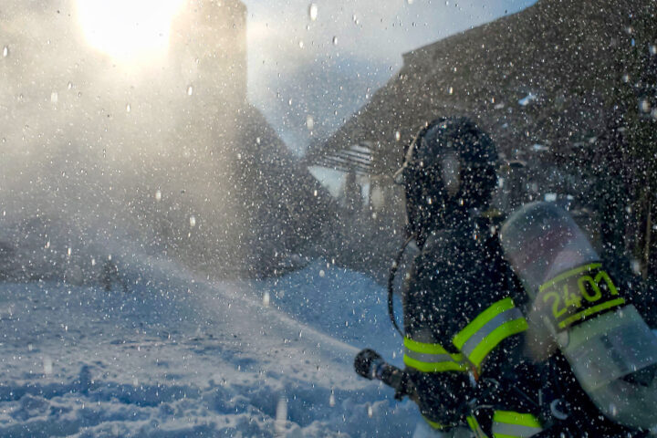 fire fighter with hose in falling ash