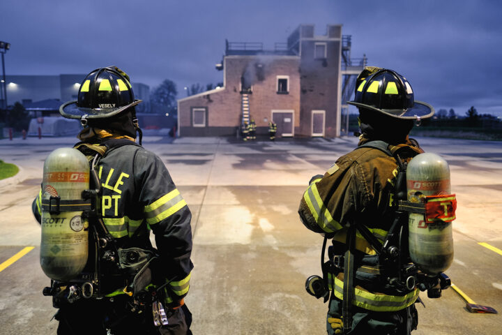 firefighters looking at building