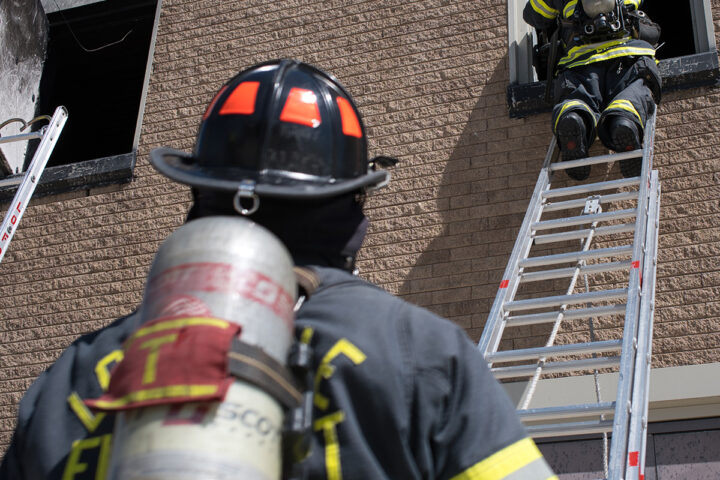 two firefighters on a ladder