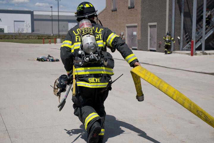 fire fighter running with hose