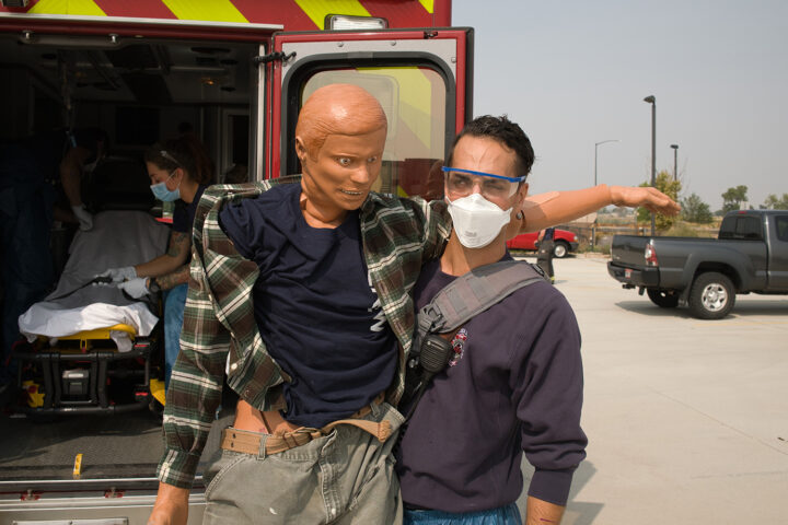 man with cpr dummy at ambulance